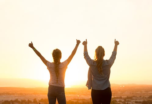 Two women looking triumphantly toward horizon