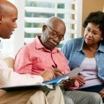 Financial Advisor Talking To Senior Couple At Home Signing Documents Sitting On Sofa about financial trust